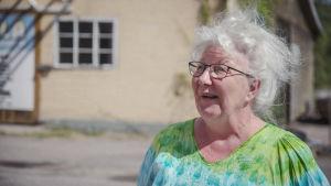 Valkohiuksinen, silmälasipäinen vanhempi nainen värikkäässä puserossa.