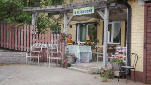 """Mies ja nainen istumassa pöydässä vaaleankeltaisen rakennuksen terassilla. Terassin yläpuolella kyltti jossa teksti """"Kylähuone""""."""