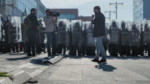 Suojapleksein varustautuneita poliiseja seisoo joukossa, edessä tv-ryhmä tekee juttua.