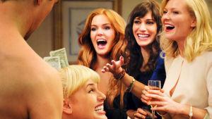 Neljä naista juhlavissa tunnelmissa nauravat kuoharilasit käsissään.