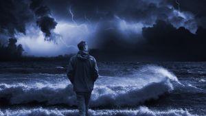Mies myrskyisen meren äärellä tumman sinertäväksi käsitellyssä kuvassa.