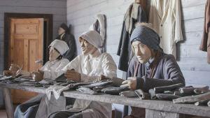 Tre uppstoppade dockor i ett museum, föreställer tre kvinnor i hucklen och förkläden som rensar sill.