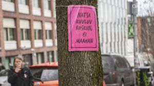 """Nainen tupakoi """"Natsa kuuluu roskiin, ei maahan"""" -kyltin vieressä."""