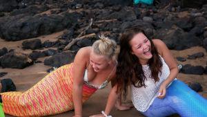 Au pairit Annika ja Emma nauravat rannalla merenneitopuvut yllään.