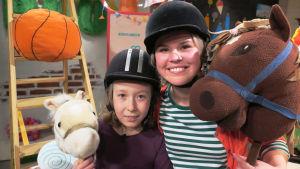 BUU-klubbens programledare Malin Olkkola står bredvid barngästen Ida, båda håller i en käpphäst och har ridhjälm på huvudet.