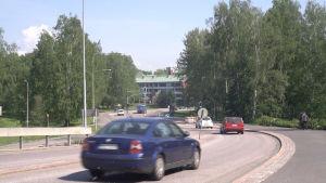 Bilar kör för Labbackavägen i Munksnäs under en solig sommardag.