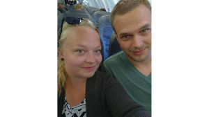 Paret Hanni och Joni sitter i ett flygplan och tar en bild på sig själv med blickarna riktade rakt mot kameran.