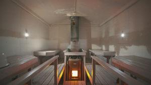 Sauna, jonka vastakkaisilla seinillä on kaksi linssiä, jotka heijastavat ulkoa maisema väärinpäin seinille.