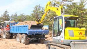 En grävmaskin puffar på en traktor med sand på släpet.