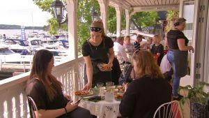 En servitris serverar mat åt två kvinnor som sitter vid ett bord på en uteservering.