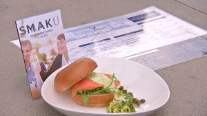 En broschyr för Smaku-matfestivalen och en hamburgare på en tallrik.