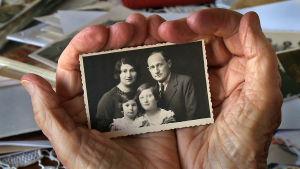 Kämmenille asetettuna mustavalkoinen kuva perheestä, jossa kaksi pientä tyttöä.