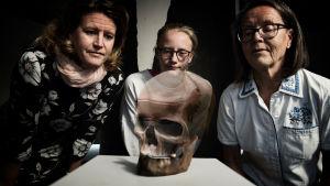 Kolme naista ja museon leukaluu, johon animoitu pääkallo.