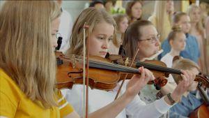 Tre unga kvinnor spelar violin i kyrka.