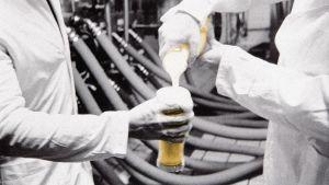 Olutpanimolla kaadetaan olutta tuoppiin, joka kuohuu yli.