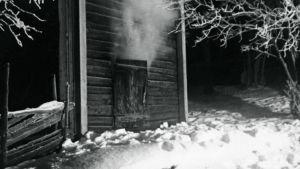 En svart-vit bild på en gammal bastu. Det är vinter och ångan stiger från öppningen till bastun.