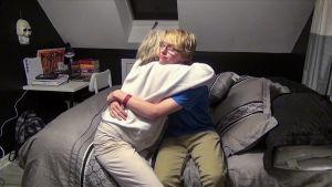 Nainen ja poika halaavat toisiaan.