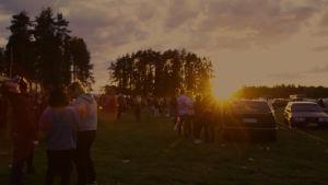 Folkmassor i kvällssolen på parkeringen utanför Klacken