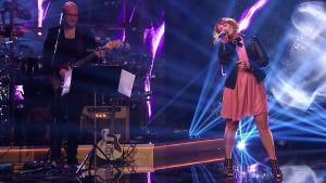Irina esiintyy, Marzi Nyman soittaa kitaraa.
