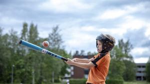 Poika lyö peäspallomailalla palloa.
