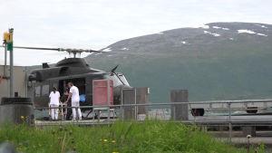 En helikopter har landat vid ett sjukhus, två sjukvårdare rullar bort en bår.