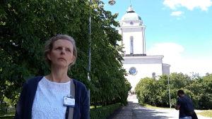 En allvarsam kvinna stor i framgrunden, i skuggan av några träd. I bakgrunden syns Sveaborgs kyrka.
