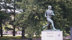 Paavo Nurmis staty framför Olympiastadio i Helsingfors. I bakgrunden syns träd.