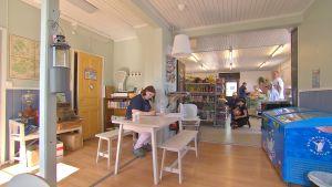 vy över lanthandeln med bord, glassförvaring och varor och kunder i bakgrunden.