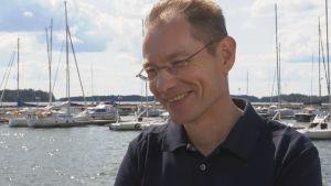 Jarkko Pajusalo, vd för Finnboat, står leende framför segelbåtar.
