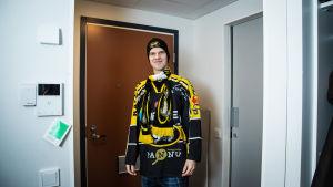 Aarne Pirkola eteisessä valmiina lähtemään jääkiekkopeliin kannatuspaita, -pipo ja -kauluhuivi yllään.