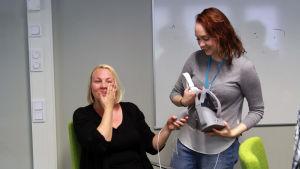 Aarnen ystävä Mirva Eteläaho pyyhkii liikutuksen kyyneleitä poskiltaan nähtyään Aarne-virtuaaliteoksen. Tuottaja Sarita Blombqvist auttaa virtuaalilasien poisottamisessa.