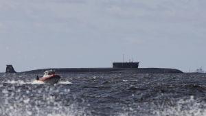 En ubåt ligger i vattnet. I förgrunden syns en motorbåt. Det är sjögång.