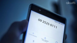 Kädessä pidetään kännykkää, näytöllä kriisipuhelimen puhelinnumero 010195202.