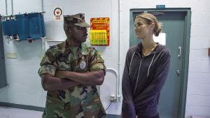 Vogue Williams seisoo käytävällä sotilaspukuun pukeutuneen miehen kanssa.
