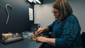 Nainen valmistaa puhallinsoittimen suukappaletta.