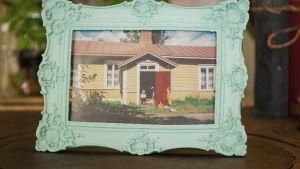 Valokuva vanhasta keltaisesta puutalosta, jonka portailla istuu lapsi.