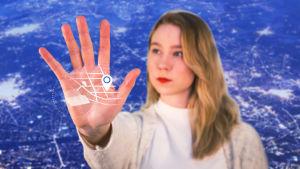 Emilia Laurila käsi ojossa, käden päällä näkyy paikannuskarttakuvaa