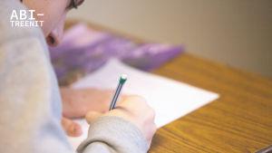 Henkilö kumartuneena kirjoittamaan paperille.