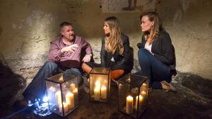 Mies ja kaksi naista kynttilöiden valossa jonkinlaisessa luolamaisessa tilassa