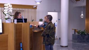En man med en flicka i famnen betjänas vid ett bankkontor.