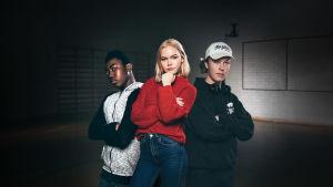 Kolme nuorta poseeraa itsevarmoina kameralle