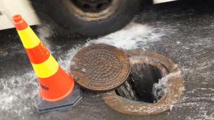 En massa vatten flödar in i en gatubrunn. Brevid den står en trafikkon. En buss kör förbi brunnen.