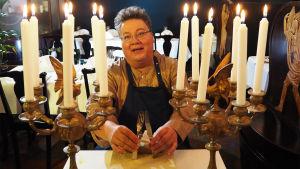 Kuvassa nukketeatterin tekijä Juha Laukkanen istuu ravintolapöydän äärellä käsissään veitsi ja haarukka ja pöydällä kaksi kynttelikköä, joissa palavat valkoiset kynttilät