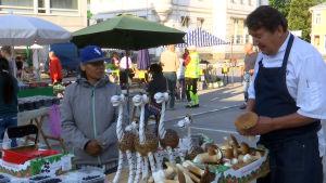 En man köper svamp i ett torgstånd.