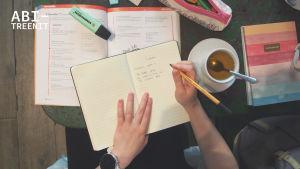 Lähikuva teekupista, vihkoista ja käsistä. Kuvassa ihminen kirjoittaa biologian muistiinpanoja vihkoon.