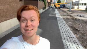 En ung man med rött hår och vit skjorta.