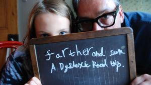 Isä ja poika pitävät kuvan edessä pientä liitutaulua, jossa on väärin kirjoitettua, lukihäiriö-aiheista tekstiä.