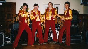 Larz-Kristerz -tanssiorkesterin jäsenet samanlaiset, puna-keltaiset esiintymisasut ylään.