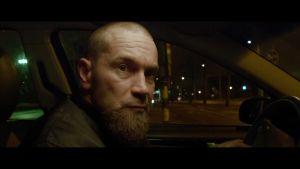 Lyhytelokuvan päähenkilö (Jukka Kärkkäinen) autossa illalla