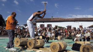 Baski seisoo tukin päällä, jota katkaisee kirveellä. Ympärillä katsojia.